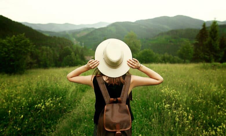 Jeune femme marchant dans un champ vert avec un chapeau et sac à dos
