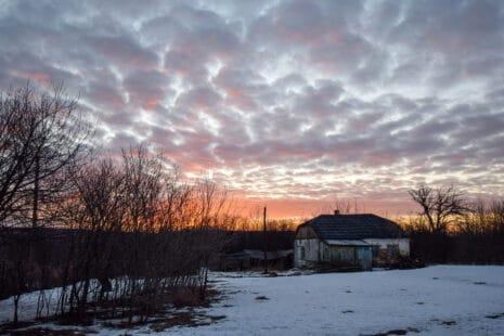 Aube, soleil levant sur une maison de camapgne et son jardin recouvert de neige