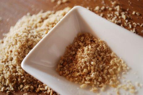 Petite coupelle blanche contenant du gomasio, parsemé sur la table
