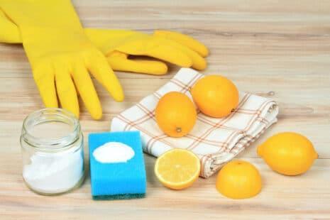 Paire de gants de viasselle jaunes, torchon à carreaux, citrons et bicarbonate de soude posé sur une éponge