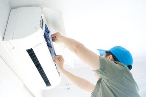 Professionnel ouvrant un climatiseur pour le nettoyer