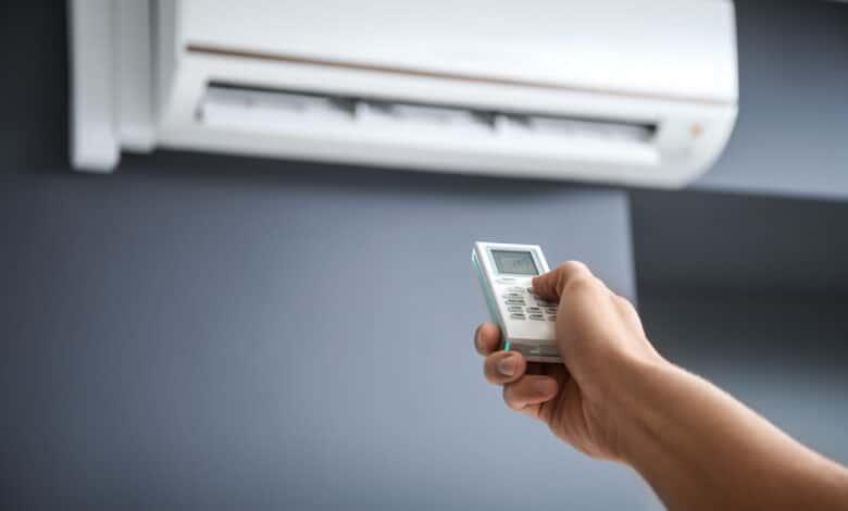 main tenant une télécommande faisant fonctionner un climatiseur