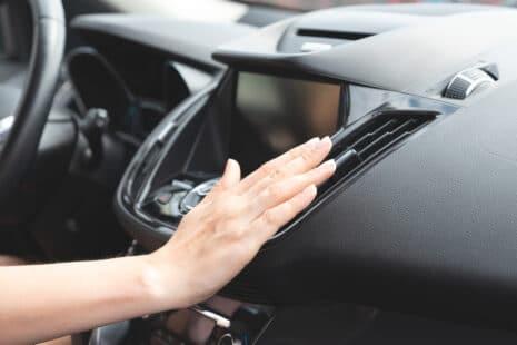Main sur la grille de ventilation d'un tableau de bord de voiture