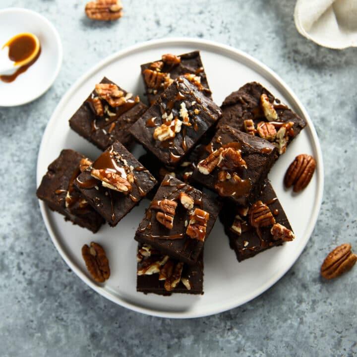 Morceaux de brownie dans une assiette avec des noix de pécan et du caramel