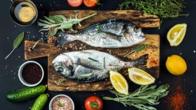 Daurades sur une planche à découper, accompagnées de quartiers de citron, thym, tomate, sauge, romarin, cornichons, sel...