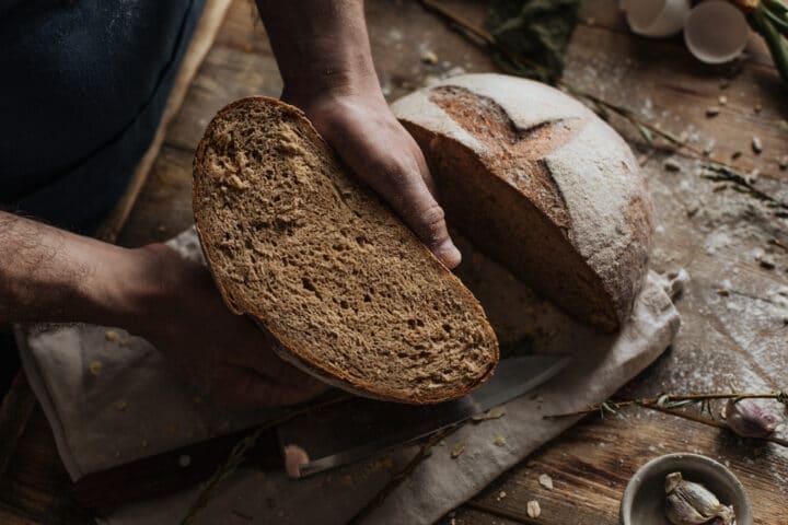 Pain de seigle coupé en 2, moitié tenue par un boulanger