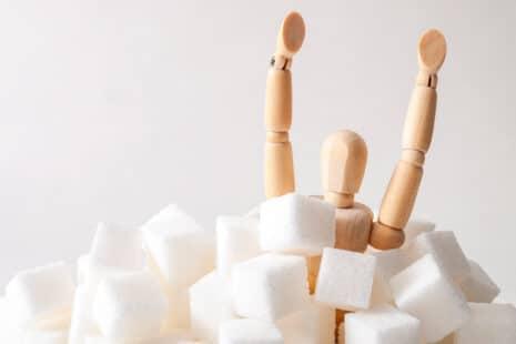 Bonhomme en bois sortant d'un tas de morceaux de sucre blanc