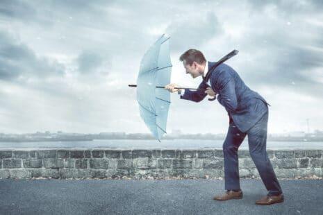 Homme d'affaire luttant contre le vent avec un parapluie