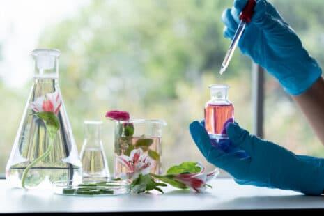 Parfum naturel : laborantin manipulant une pipette avec falcon, tube à essai, becher, plantes, eaux florales
