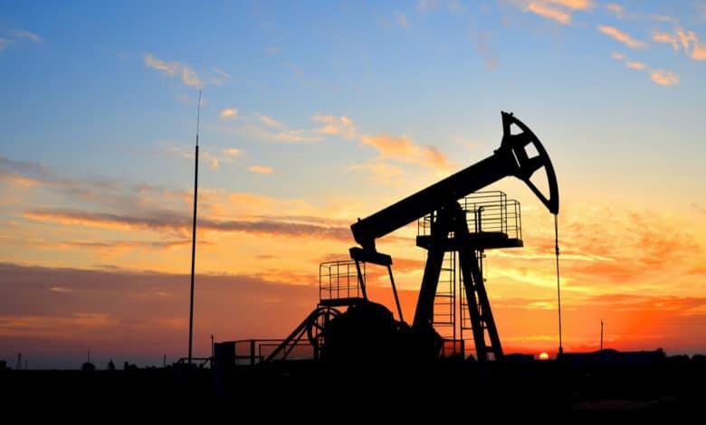Puits de pétrole sur un coucher de soleil jaune et rose