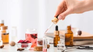 Parfum naturel : personne confectionnant un parfum maison : pipette, flacon, pot en verre, fleurs, plantes