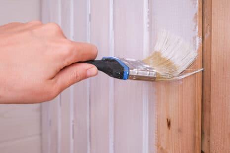 Main tenant un pinceau et peignant un mur en bois avec de la peinture écologique blanche