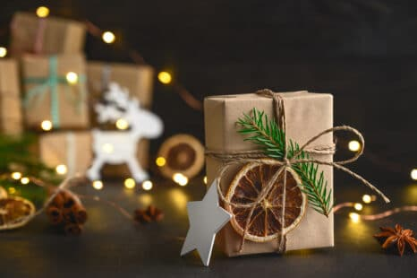 Décoration de Noël naturelle ; papier kraft marron, tranche d'orange séchée, branche de pin, étoile blanche, renne blanc, lumière, bricolage écologique