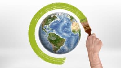 Main tenant un pinceau, entourrant de vert un dessin de la planète Terre