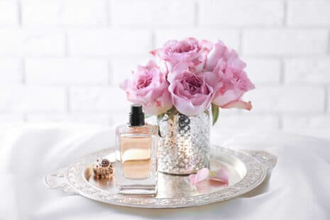 Plateau avec un bouquet de fleurs mauves, un bijou et un élégant flacon de parfum