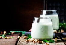 Deux verres de lait de pistache, couleur verte, avec des éclats de psitache autour