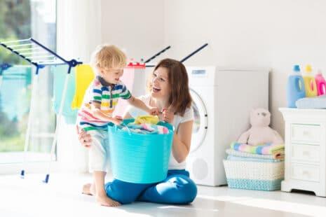 Jeune femme avec son enfant sortant le linge de la machine à laver pour l'étendre