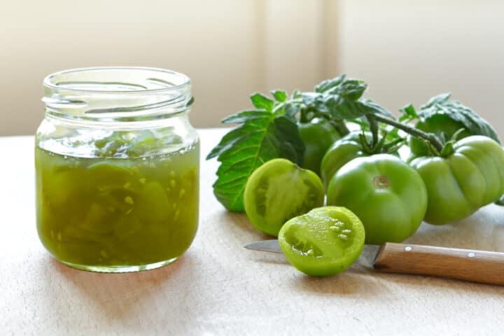 Bocal en verre de confiture de tomates vertes avec une branche de tomates vertes en grappe