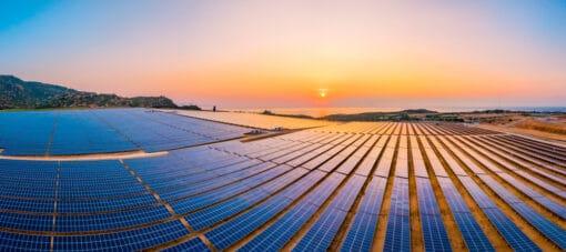 Champs de panneaux solaires se terminant à côté de la mer, coucher de soleil en arrière plan