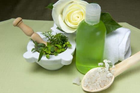 Plantes aromatiques dans un pilon, pétales de rose, sel d'Espom et bouteille d'adoucissant