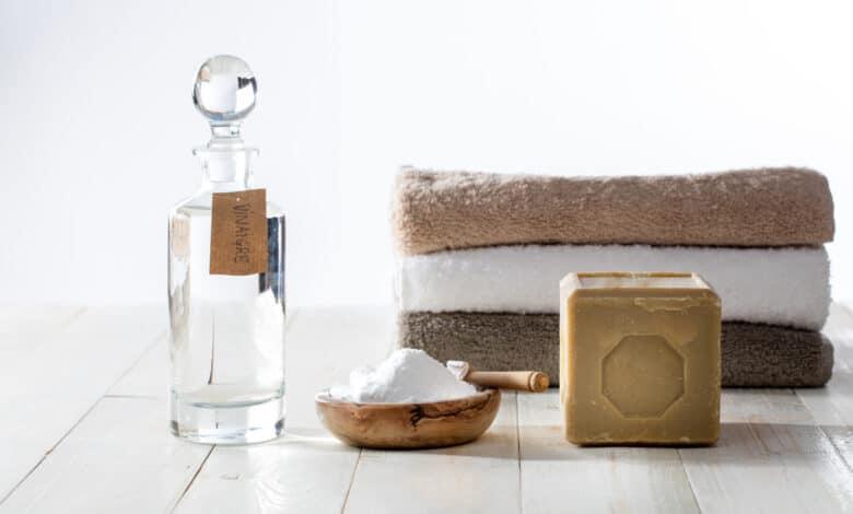 Pile de linge de maison avec bouteille en verre, savon de marseille et coupelle remplie de bicarbonate