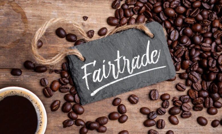 """petite ardoise """"Faire Trade"""" (commerce équitable"""" posée sur une table au milieu de grains de café, à côté d'une tasse de café"""