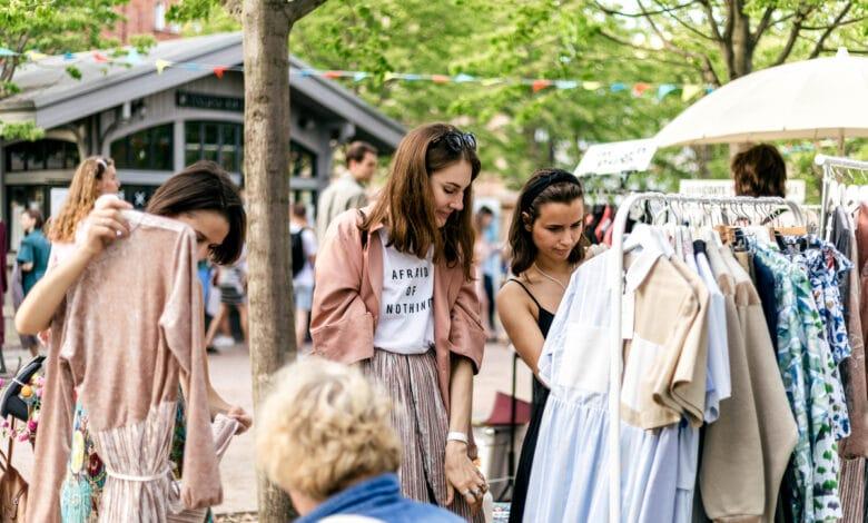 Jeunes femmes dans un vide-grenier choisissant des vêtements