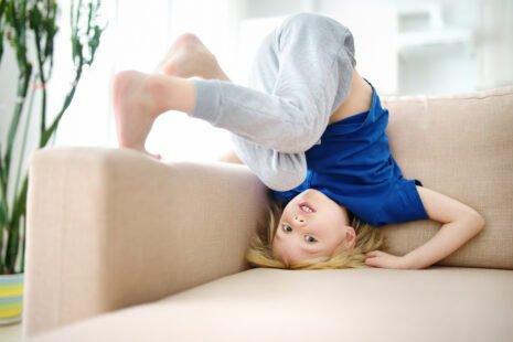 Enfant hyperactif retourné sur un canapé