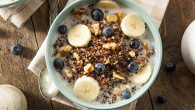 Bol de petit-déjeuner contenant du quinoa, du lait de quinoa, des céréales, des rondelles de bananes