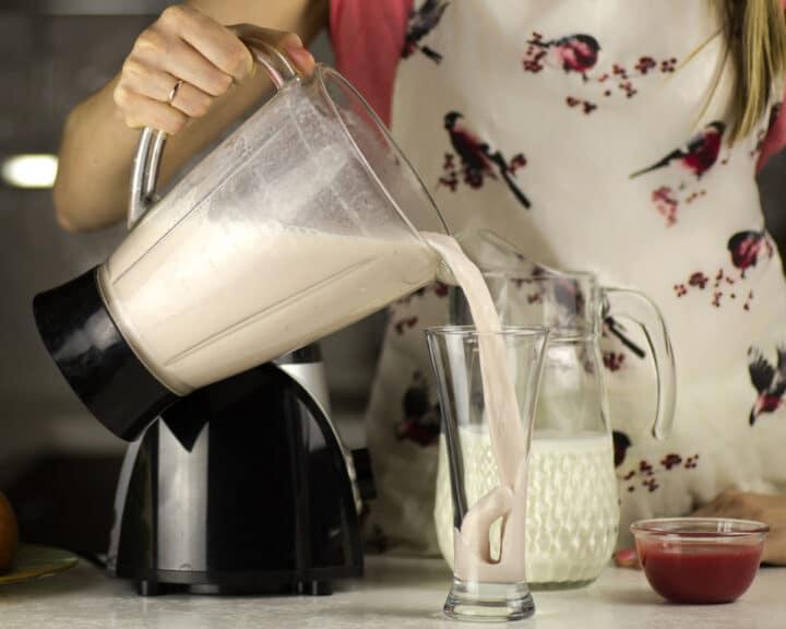 Jeune femme tenant un blender et versant du lait végétal dans un verre