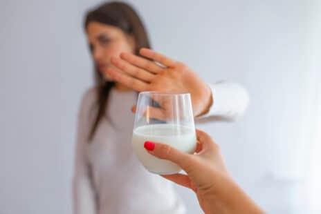 Un verre de lait tendu à une femme qui le refuse en levant sa main