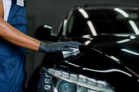 Ouvrier frottant avec un tissu le capot d'une belle voiture