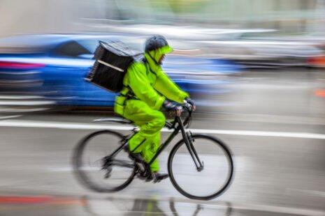 Livreur à vélo ayant une combinaison intégrale verte sous la pluie