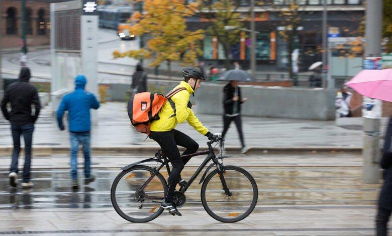 Homme sur un vélo avec une veste jaune et un sac orange