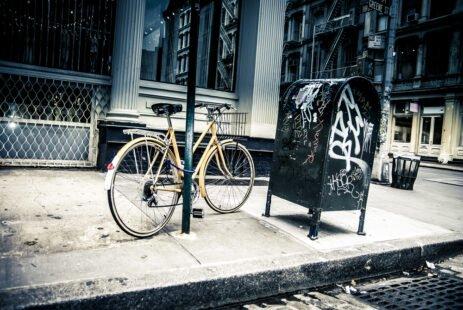 Photo sépia : vélo attaché à l'aide d'un anti-vol U à un potteau