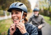 Couple à vélo, la femme attache son casque vélo